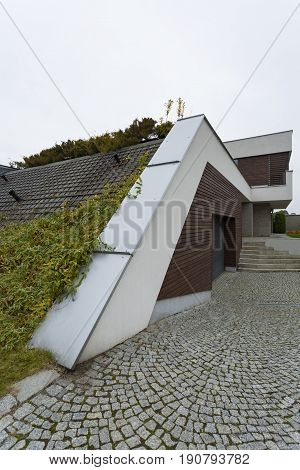 Modern garage with sloping roof with grass on it