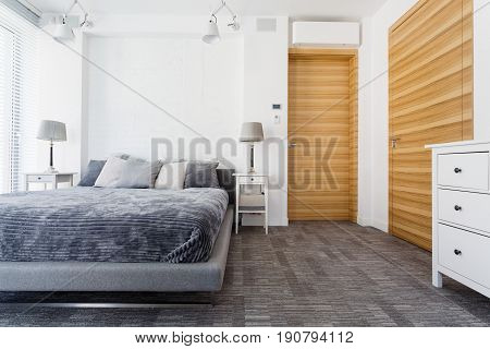 Bright bedroom with king-size bed commode lamps and wooden doors