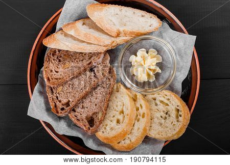 Top view of sliced wholegrain bread ciabatta and rye spikelets bread with butter on black wooden background. Bakery products. Hot and healthy breakfast top view flat lay