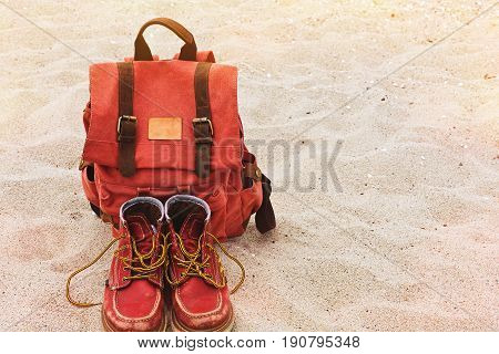 Old fashioned backpack and boots careless left on the sand beach