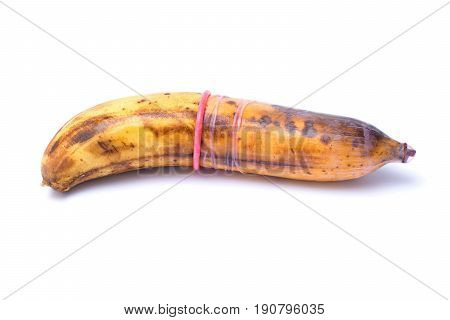 Rotten banana curve wearing a condom isolate on white background
