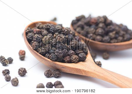 Close up peppercorns in wooden spoon isolated on white background