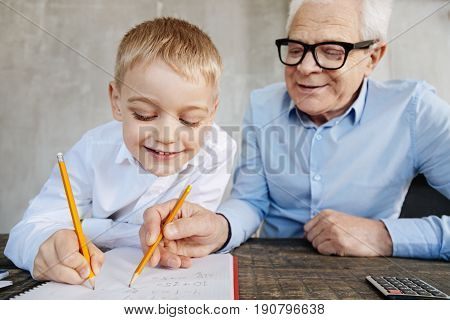 Sharing his wisdom. Emotional gifted adorable kid fulfilling his home assignment while his grandpa watching him doing it and correcting his mistakes