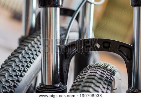 Bicycle wheel and tire close up view low depth. Bicycle fork with oil damper in the background
