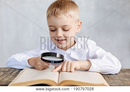Tiny characters. Clever interested productive kid perusing pages of an old book while sitting at the table and looking through a magnifying glass