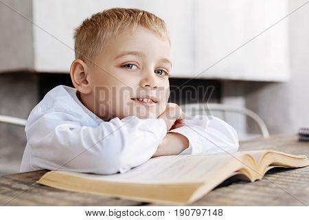 Bright child. Talented diligent brilliant kid taking a moment for resting while reading an old book and sitting at the table