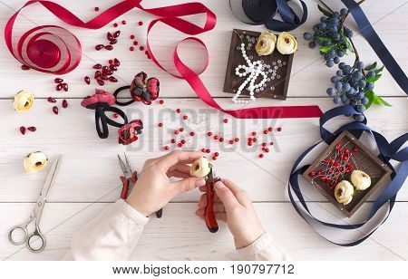 Woman making jewelry, home workshop. Artisan pov, female hands creating accessory with beads and ribbons, top view. Beauty, creativity, handicraft concept poster
