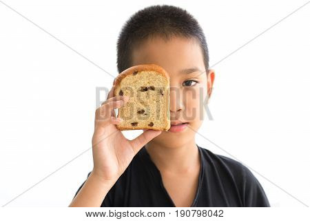 Asian boy shutting eyes with whole wheat raisin loaf bread isolated on white background
