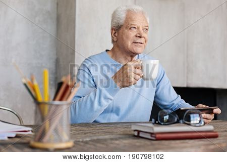 No hurry. Handsome admirable elderly man spending an active morning in his home office while perusing some news using his laptop