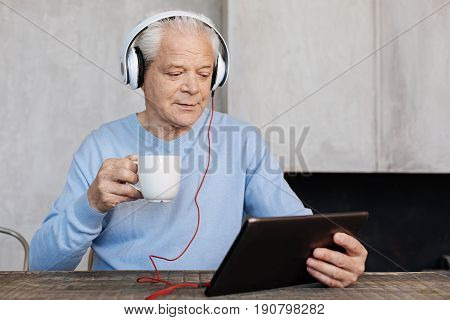 Focused on a screen. Elderly bright savvy man using a tablet and wearing headphones for watching videos while drinking coffee