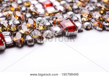 Colorful gemstones variety on white background, free space. Assortment of bright mounted gemstones, jewelry production concept