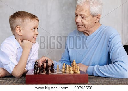 Game of intellectuals. Active wise mature man making a little lecture about an intellectual game while deciding playing chess with him