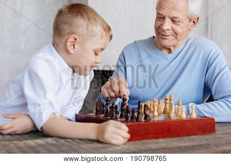 Careful what you do next. Observant wise elderly gentleman making a final move in their game of chess while teaching his grandchild playing it