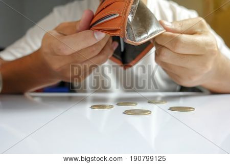 Coin falling from wallet - Little money concept - closeup