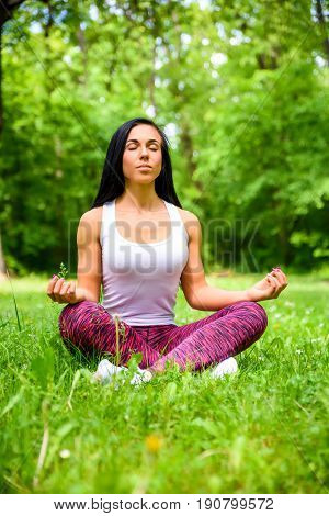 A beautiful young sporty girl sitting and meditating on the grass in the woods while wearing a leggings and a top
