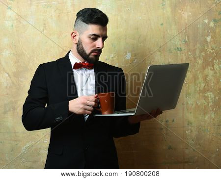 Bearded Project Manager With Serious Face Puts Coffee On Laptop
