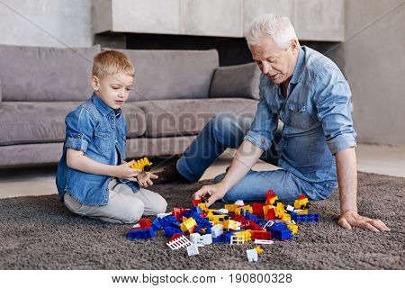Development in game. Creative vibrant cheerful kid visiting his grandpa and playing with him using construction set