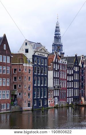 dutch canalside houses with church spire in amsterdam