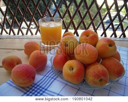 Apricots in a vase and a glass of juice on a veranda table.