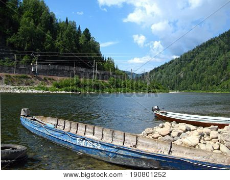 Boats on the shore of the taiga river in the foothills of the Kuznetsk Alatau