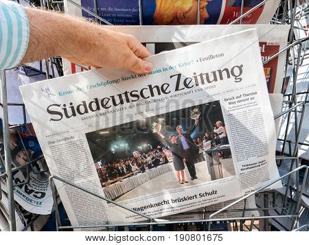 PARIS FRANCE - JUN 12 2017: Man point of view personal perspective buying at press kiosk Suddeutsche Zeitung newspaper with reactions to German legislative election 2017 a day after first round