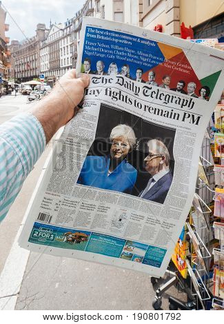 PARIS FRANCE - JUN 12 2017: Man point of view personal perspective buying at press kiosk The Daily Telegraph newspaper with reactions to United Kingdom general election of 2017 - Theresa May fights to remain PM
