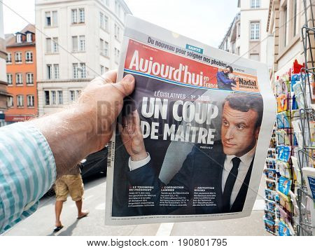 PARIS FRANCE - JUN 12 2017: Man point of view personal perspective buying at press kiosk Aujourd'Hui newspaper with reactions to French legislative election 2017 a day after first round