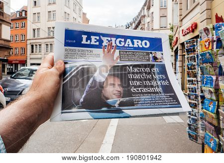 PARIS FRANCE - JUN 12 2017: Man point of view personal perspective buying at press kiosk Le Figaro newspaper with reactions to French legislative election 2017 - Emmanuel macron majority