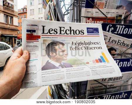 PARIS FRANCE - JUN 12 2017: Man point of view personal perspective buying at press kiosk Les Echos newspaper and Effect Macron with reactions to French legislative election 2017 a day after first round