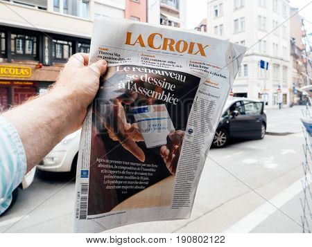 PARIS FRANCE - JUN 12 2017: Man point of view personal perspective buying at press kiosk French newspaper La Croix with reactions to French legislative election 2017 a day after first round