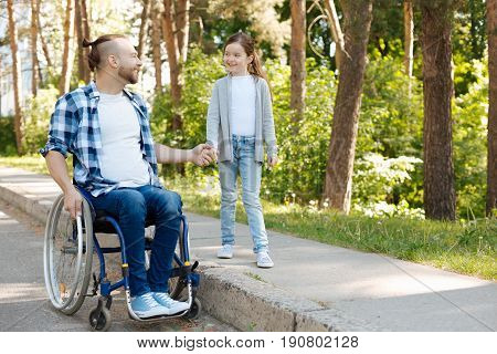 Go for a walk. Disabled man using his wheelchair for movement in park keeping smile on his face while holding hand with his daughter