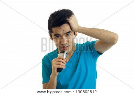 Portrait of guy with black hair who keeps hand behind your head and shaves a beard trimmer close-up isolated on white background