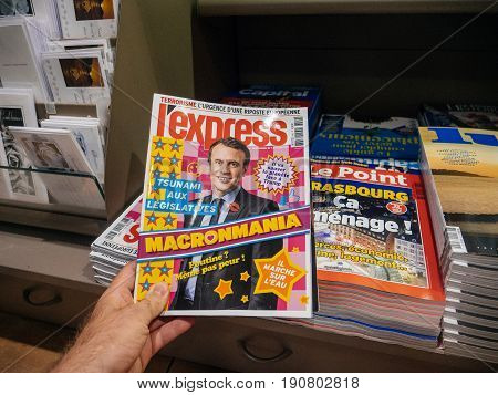 PARIS FRANCE - JUN 12 2017: Man point of view personal perspective buying at press kiosk magaizne L'Express with Macronmania and Emmanuel Macron picture with reactions to French legislative election 2017 a day after first round