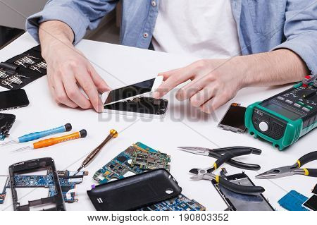 Repairman disassembling smartphone for inspecting. Technician fixing broken phone, electronics repair service