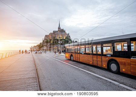 MONT SAINT MICHEL, FRANCE - May 29, 2017: View on the famous Mont Saint Michel island with motion blurred shuttle bus designed for transporting tourists from Caen to Saint Michel