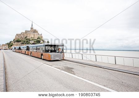 MONT SAINT MICHEL, FRANCE - May 30, 2017: View on the famous Mont Saint Michel island with tourists and shuttle bus designed for transporting tourists from Caen to Saint Michel
