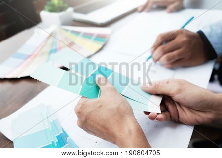 Engineer and architect select color for house project. Graphic design and color swatches and pens on a desk. Architectural drawing with work tools and accessories.