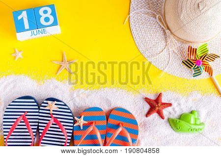 June 18th. Image of june 18 calendar on yellow sandy background with summer beach, traveler outfit and accessories. Summertime concept.