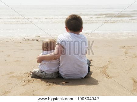 Ten year old with baby brother sitting on the beach