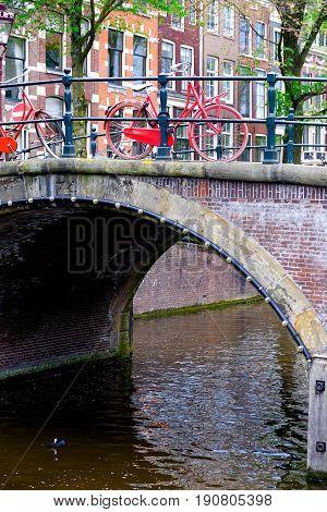 red bicycle padlocked to bridge railings in amsterdam