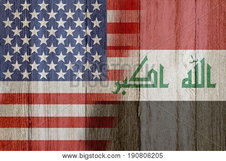 Relationship between the USA and Iraq The flags of USA and Iraq merged on weathered wood