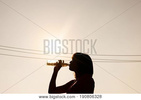 Female drinking water in hot summer - heat stroke concept