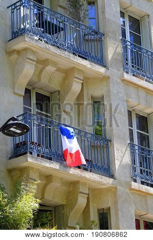 a french national flag draped over residential balcony railings