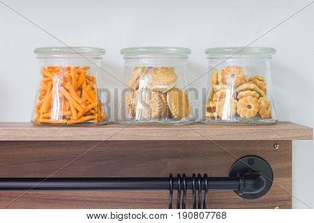 salty crackers in glass bottle on wooden shelf