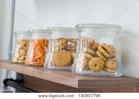 salty crackers in glass bottle on wooden shelf. Perspective
