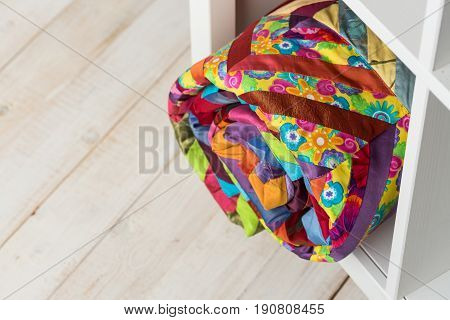 patchwork, sewing and fashion concept - bright colorful quilt at white shelves with storage compartment in store, white floor in a warehouse of finished stitched textile products, top view.