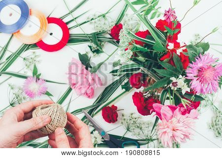 The hands of a florist male making beautiful flower composition the concept of flower design ikebana. top view flat lay