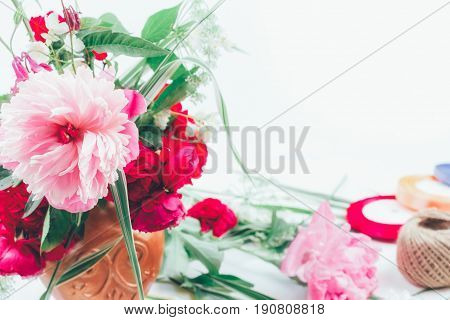 floral design. floral arrangement from beautiful bouquet of pink flowers peons cornflowers and red roses on white background with space for text