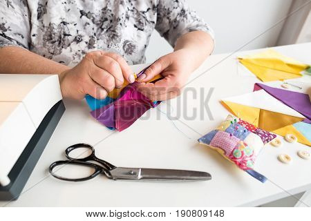 needlework and hand quilting in the workshop of a tailor woman - close up on hands of a seamstress combine the pattern pieces are sewn of colored fabrics on the desktop of thread, scissors.