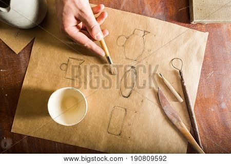 pottery, sculpting tools, ceramics art concept - top view on pencil drawing of clay jugs, design and engineering of products, cup and pencil on the wooden table, brown background